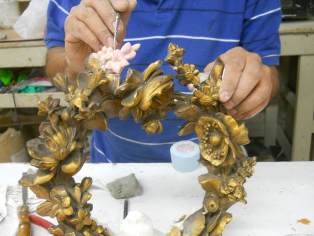 Gilding of floral element on a frame restoration