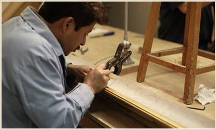 A skilled craftsman carefully marks a cut on a frame
