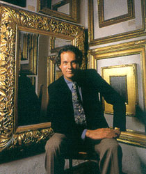 Eli Wilner sitting in a gallery surround by antique picture frames