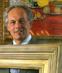 Eli Wilner standing with a gilded picture frame