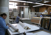 Skilled craftspeople work in the frame restoration studio