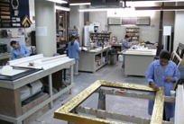 An expert gilder works in the frame restoration studio